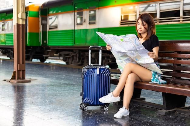Aziatische vrouw die een kaart bij een treinstation kijkt.