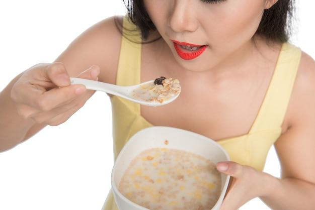Aziatische vrouw die een kom ontbijtgranen of muesli eet als ontbijt
