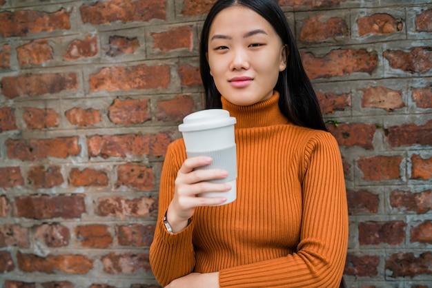 Aziatische vrouw die een kop van koffie houdt.