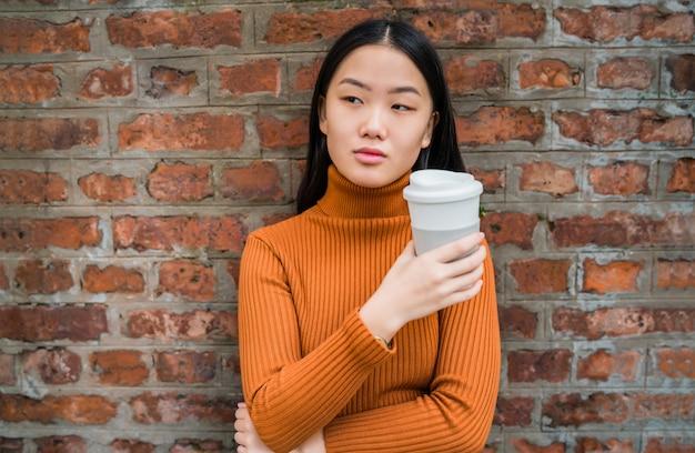 Aziatische vrouw die een kop van koffie houdt