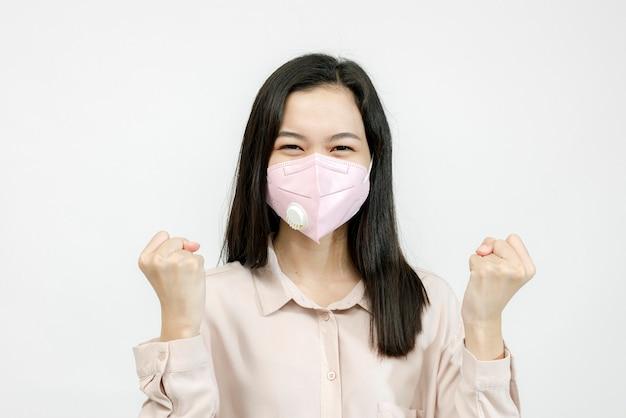 Aziatische vrouw die een masker draagt dat haar handen opsteekt