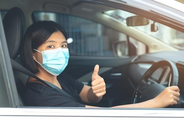 Aziatische vrouw die een masker draagt dat in de auto zit om coronavirus te voorkomen