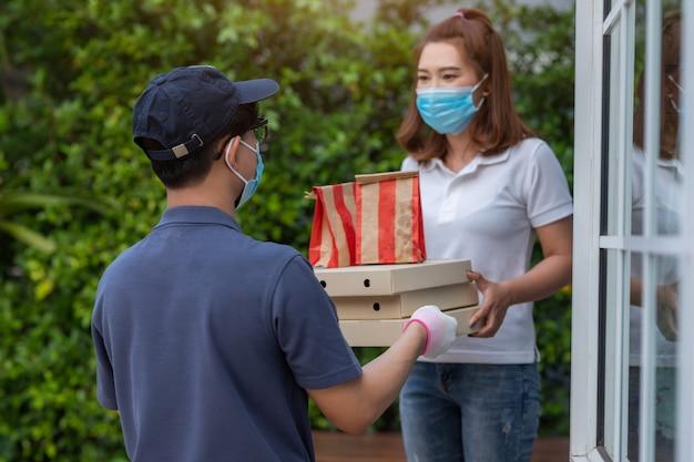 Aziatische vrouw die een masker draagt dat voedselpakket van van de het conceptdienst van de leveringsman thuis de quarantainevirus van de pandemisch coronavirus [covid-19] ontvangt.