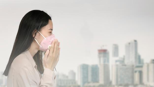 Aziatische vrouw die een masker draagt en hoest in een vervuilde stad