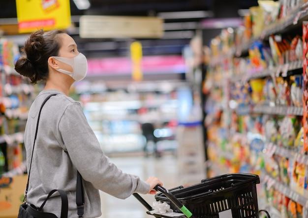 Aziatische vrouw die een masker in de supermarkt draagt