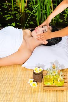 Aziatische vrouw die een massage in het tropische plaatsen heeft