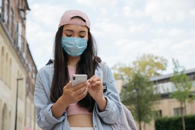 Aziatische vrouw die een medisch beschermingsmasker draagt dat buitenshuis mobiele telefoon gebruikt