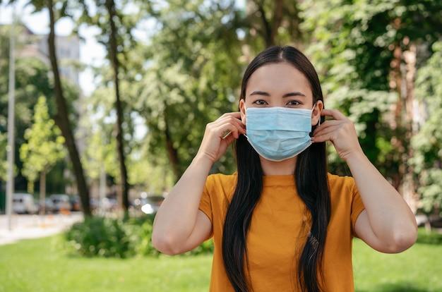 Aziatische vrouw die een medisch masker draagt dat buiten naar de camera kijkt