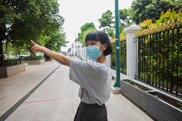 Aziatische vrouw die een medisch masker draagt, reist door openbare plaatsen