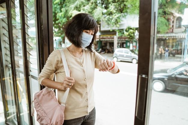 Aziatische vrouw die een openbaar vervoer berijdt dat gezichtsmasker draagt tijdens pandemie