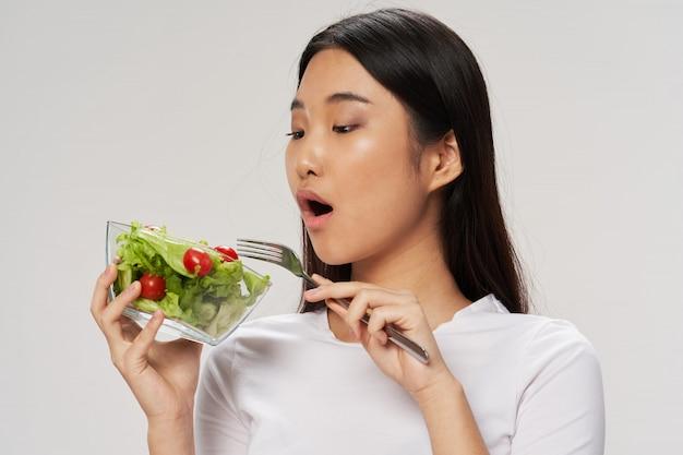Aziatische vrouw die een salade eet