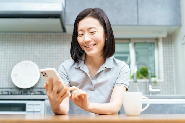 Aziatische vrouw die een smartphone in de ruimte bedient