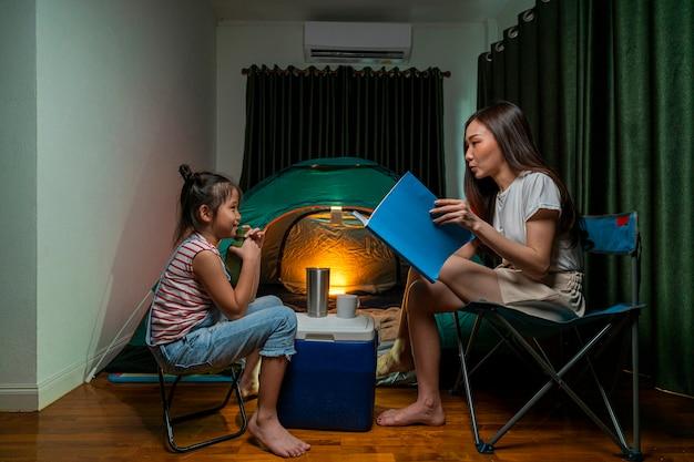 Aziatische vrouw die een sprookjesverhaal voorleest aan haar dochter en plezier heeft met kampeertent in hun slaapkamer, een staycation-levensstijl een nieuwe norm voor sociale afstand nemen in een uitbraak van het coronavirus