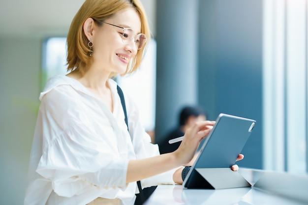 Aziatische vrouw die een tablet-pc in de stad bedient