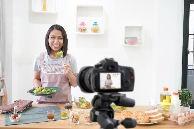 Aziatische vrouw die een vlog-video digitale camera voor haar blog maken die in de keukenruimte koken