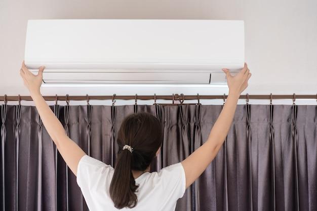 Aziatische vrouw die een vuil en stoffig airconditionerfilter in slaapkamer verandert. vrouw die een vuil luchtfilter in airconditioner verwijdert.