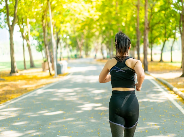 Aziatische vrouw die en bij park aanstoot loopt