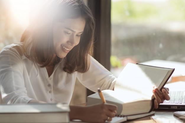 Aziatische vrouw die en boek met gelukkig werkt leest.
