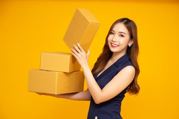Aziatische vrouw die en de doos van het pakketpakket glimlacht houdt die op geel wordt geïsoleerd.