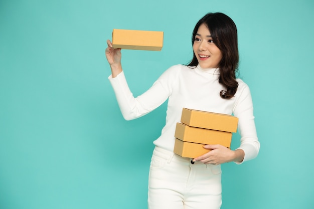 Aziatische vrouw die en de doos van het pakketpakket glimlacht houdt die op lichtgroene achtergrond wordt geïsoleerd.