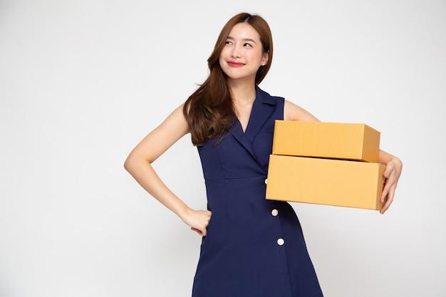 Aziatische vrouw die en de doos van het pakketpakket glimlacht houdt die op witte achtergrond wordt geïsoleerd