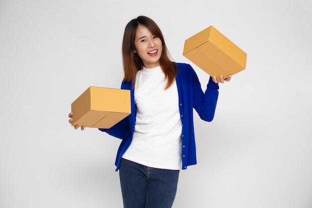Aziatische vrouw die en de doos van het pakketpakket glimlacht houdt die op witte muur wordt geïsoleerd.