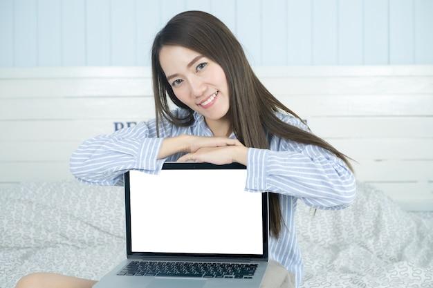 Aziatische vrouw die en het lege laptop computerscherm glimlacht toont in haar slaapkamer.