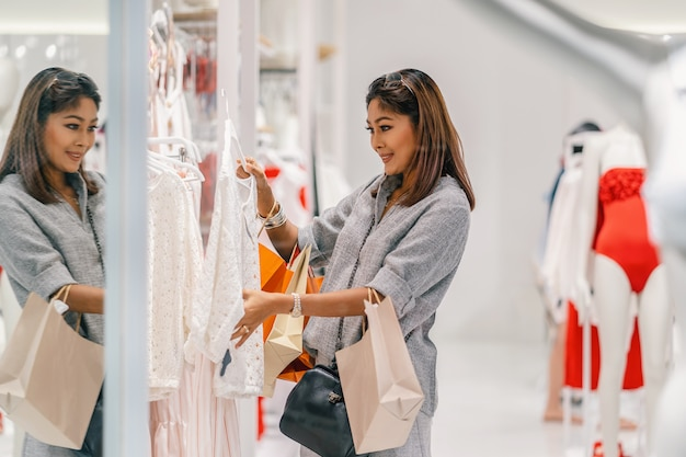 Aziatische vrouw die en het ondergoed in opslagwinkel met gelukkige actie kijken bekijken op afdelingscentrum