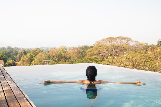 Aziatische vrouw die en in zwembad op dakbovenkant zwemt ontspant
