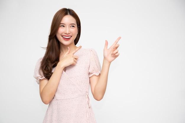 Aziatische vrouw die en naar lege exemplaarruimte glimlacht richt die op witte muur wordt geïsoleerd