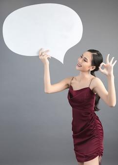 Aziatische vrouw die en omhoog aan toespraakbel met lege ruimte voor tekst houden kijken