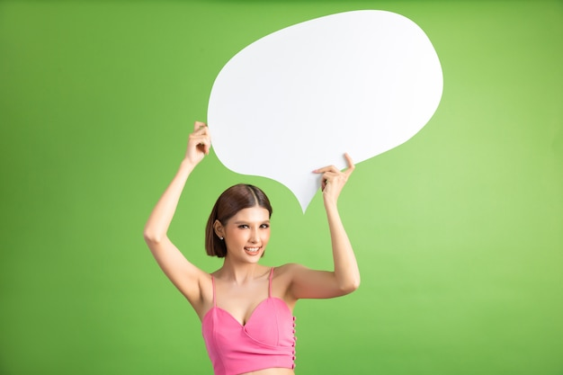 Aziatische vrouw die en omhoog aan toespraakbel met lege ruimte voor tekst op groen houden kijken