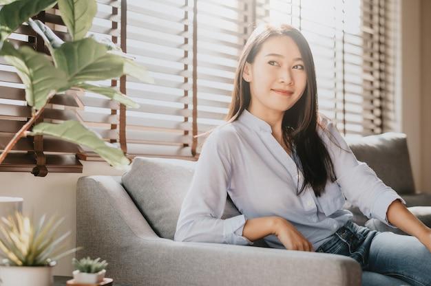 Aziatische vrouw die en op haar laag thuis ontspant glimlacht
