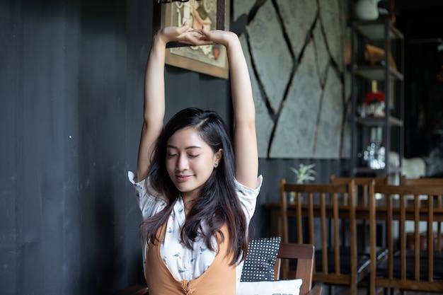 Aziatische vrouw die en zich in het huisbureau uitrekt glimlacht