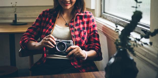 Aziatische vrouw die filmcamera in de koffie van de koffiewinkel met behulp van