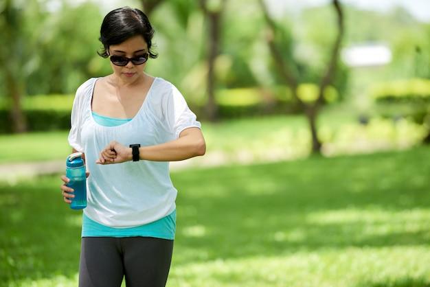 Aziatische vrouw die fitnessarmband controleert