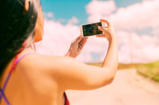 Aziatische vrouw die foto met telefoon neemt