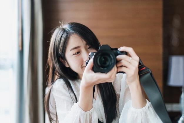 Aziatische vrouw die foto neemt door spiegelloze digitale camera, met lachend gezicht