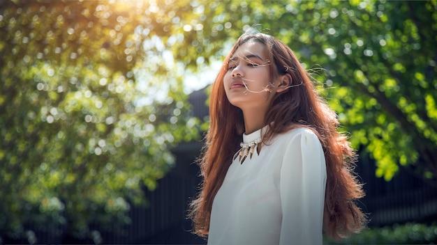 Aziatische vrouw die frisse lucht met de wind in opublic park briest