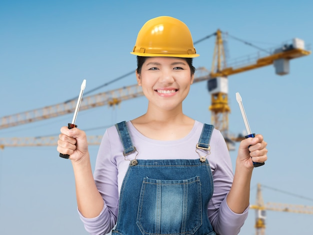 Aziatische vrouw die gele veiligheidshelm met bouwwerfachtergrond draagt