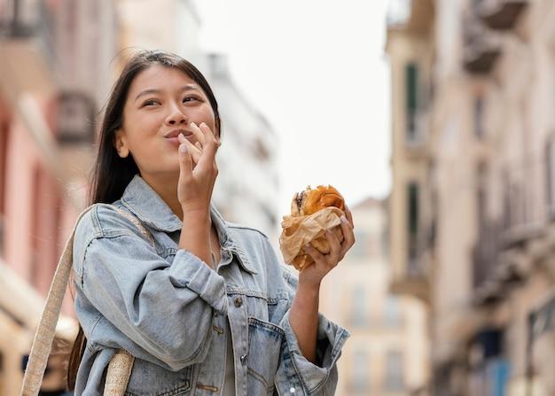 Aziatische vrouw die gelukkig is na het kopen van straatvoedsel