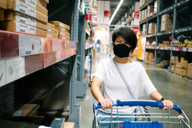 Aziatische vrouw die gezichtsmasker draagt dat ding in warenhuis selecteert