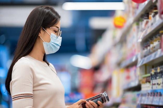 Aziatische vrouw die gezichtsmasker draagt dat in supermaket winkelt tijdens coronavirus