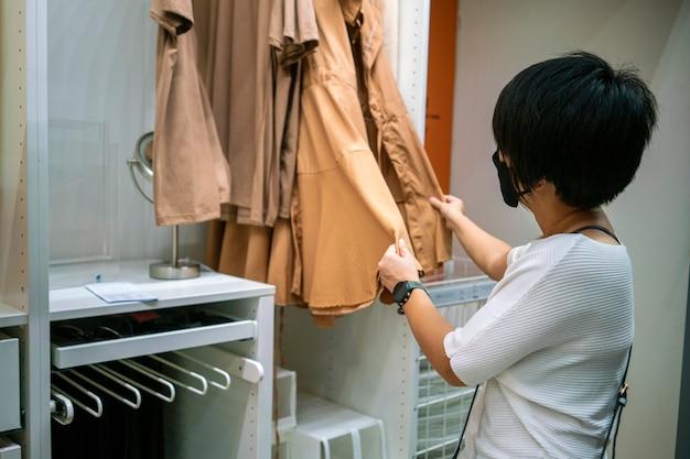 Aziatische vrouw die gezichtsmasker draagt die kleren in winkelcentrum koopt tijdens coronavirus-pandemie. kruidenierswinkelcentrum, supermarkt, bescherming en preventieconcept