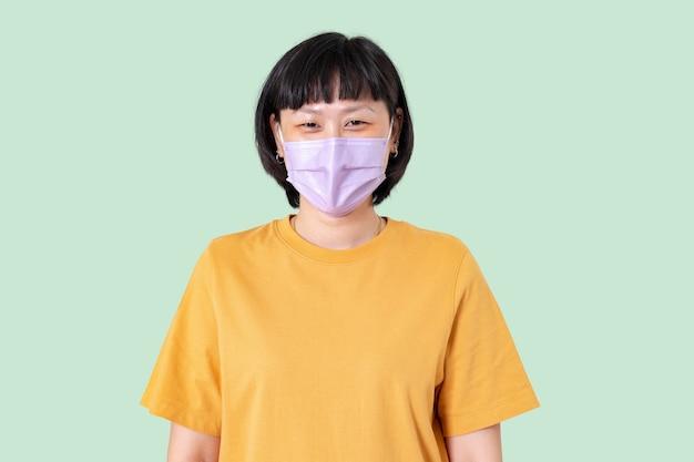Aziatische vrouw die gezichtsmasker draagt in het nieuwe normaal Gratis Foto