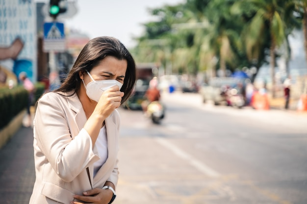 Aziatische vrouw die gezichtsmasker draagt om tegen virus te beschermen. covid-19 coronavirus-concept.