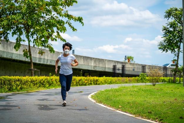 Aziatische vrouw die gezichtsmasker draagt terwijl ze in openbaar park rent na coronavirus-uitbraak en stadsvergrendeling een nieuw normaal leven. sociale afstand nemen, nieuwe normale, covid-19 of lopende concepten