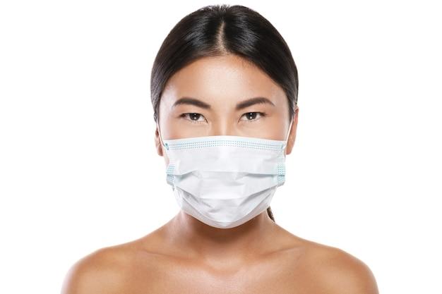 Aziatische vrouw die gezichtsmasker draagt voor bescherming tegen luchtverontreiniging of virusepidemie op witte muur