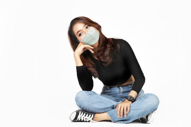 Aziatische vrouw die gezichtsmasker met geïsoleerde vrijetijdskleding draagt