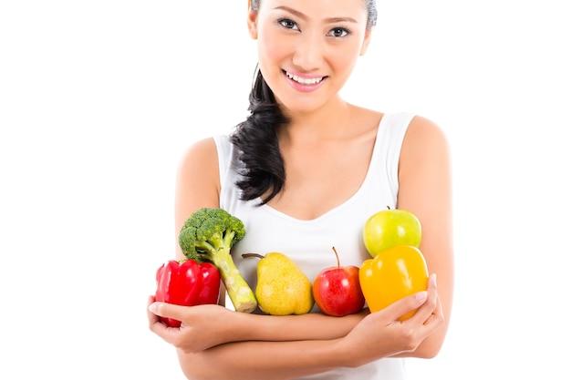 Aziatische vrouw die gezond fruit eet